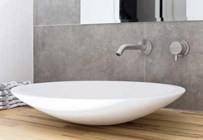 Witte waskom op houten badkamermeubel
